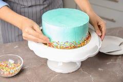 Vrouw die verse heerlijke verjaardagscake in keuken verfraaien stock foto