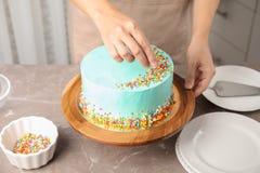 Vrouw die verse heerlijke verjaardagscake in keuken verfraaien stock foto's
