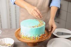 Vrouw die verse heerlijke verjaardagscake in keuken verfraaien royalty-vrije stock afbeeldingen