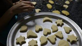 Vrouw die verse koekjes in bakselschotel zetten De koekjes van Kerstmis stock footage