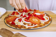 Vrouw die verse paprika voor ruwe pizza toevoegen Royalty-vrije Stock Foto
