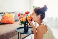 Vrouw die verse rozen in vaas op lijst ruiken Huisvrouw die behaaglijkheid in flat behandelen Binnenland en decor stock fotografie