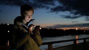 Vrouw die verticale smartphone op dek van cruiseschip gebruiken bij nacht stock videobeelden