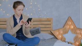 Vrouw die verticale zwarte smartphone thuis gebruiken stock videobeelden