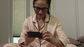 Vrouw die videobericht op smartphone toont stock videobeelden