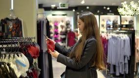 Vrouw die vinden nieuw lingerieondergoed in supermarktwandelgalerij stock footage