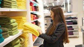 Vrouw die vinden nieuwe handdoeken in een winkel van de opslagsupermarkt stock video
