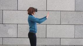 Vrouw die vinger gebruiken om bij het denkbeeldige paneel bekijken op VR-apparaat in openlucht betrekking te hebben Vergroot virt stock videobeelden