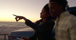 Vrouw die vinger richten en iets tonen aan de mens op strand 4k stock video