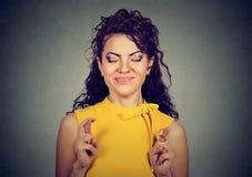 Vrouw die vingers, gesloten ogen kruisen, hopen, die wens maken stock afbeelding
