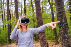 Vrouw die virtuele werkelijkheidsbeschermende brillen buiten in de lenteaard draagt Royalty-vrije Stock Afbeeldingen