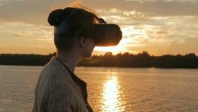 Vrouw die virtuele werkelijkheidsglazen op dek van cruiseschip gebruiken bij zonsondergang stock footage