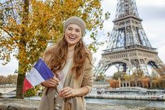 Vrouw die vlag op dijk tonen dichtbij de toren van Eiffel, Parijs royalty-vrije stock afbeelding