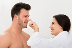 Vrouw die vochtinbrengende crème op man neus toepassen stock foto