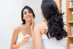 Vrouw die vochtinbrengende crème toepast royalty-vrije stock foto