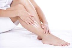 Vrouw die vochtinbrengende crèmeroom op de benen toepast Royalty-vrije Stock Afbeeldingen