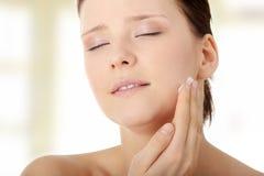 Vrouw die vochtinbrengende crèmeroom op gezicht toepast stock afbeelding