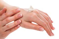 Vrouw die vochtinbrengende crèmeroom op handen toepassen royalty-vrije stock afbeelding