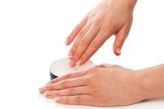 Vrouw die vochtinbrengende crèmeroom op handen toepassen stock afbeeldingen