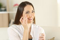Vrouw die vochtinbrengende crèmeroom op het gezicht toepassen royalty-vrije stock foto's