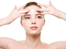 Vrouw die vochtinbrengende crèmeroom op het voorhoofd toepast Royalty-vrije Stock Foto's