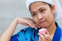 Vrouw die vochtinbrengende crèmeroom toepast stock afbeelding
