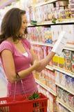 Vrouw die voedsel etikettering controleert Stock Foto