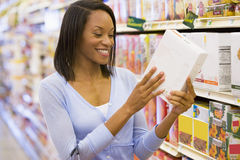 Vrouw die voedsel etikettering in supermarkt controleert Royalty-vrije Stock Afbeelding