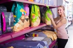 Vrouw die voedsel voor huisdieren onderzoeken stock afbeeldingen