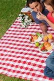 Vrouw die voedsel zet in haar vriendenmond Royalty-vrije Stock Foto's