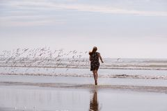 Vrouw die Vogels op Strand achtervolgen stock afbeelding