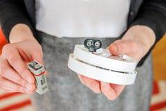 Vrouw die 9 voltbatterij installeren in rookdetector Royalty-vrije Stock Foto's