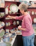 Vrouw die voor aardewerk winkelt Royalty-vrije Stock Afbeelding