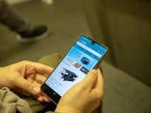 Vrouw die voor Echo Dot op de mobiele toepassing van Amazonië op het iPhonescherm winkelen terwijl het omzetten op metro royalty-vrije stock afbeeldingen