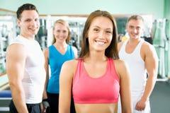 Vrouw die voor een groep gymnastiekmensen glimlachen stock afbeelding