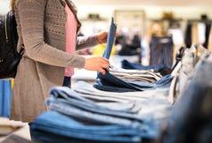 Vrouw die voor jeans in manieropslag winkelen stock foto's