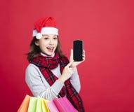 Vrouw die voor Kerstmisgiften door slimme telefoon winkelen Stock Foto's