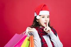Vrouw die voor Kerstmisgiften winkelen met geheim gebaar royalty-vrije stock foto's