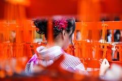 Vrouw die voor kimono in het heiligdom oppassen Stock Foto