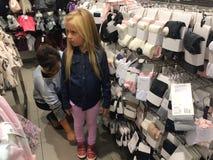 Vrouw die voor kinderenkleren winkelen Stock Foto's