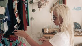 Vrouw die voor kleding in kledingsdetailhandel winkelt Mooi Kaukasisch klantenmeisje die rode kleding in winkel kiezen tijdens stock footage