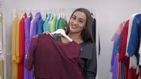 Vrouw die voor kleding in kledingsdetailhandel winkelt Mooi multiraciaal Arabisch Kaukasisch klantenmeisje die rood kiezen stock videobeelden