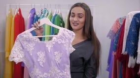 Vrouw die voor kleding in kledingsdetailhandel winkelt Mooi multiraciaal Arabisch Kaukasisch klantenmeisje die rood kiezen stock video