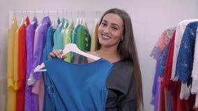 Vrouw die voor kleding in kledingsdetailhandel winkelt Mooi multiraciaal Arabisch Kaukasisch klantenmeisje die rood kiezen stock footage