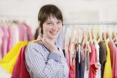 Vrouw die voor kleren winkelt Stock Foto