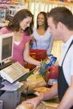 Vrouw die voor kruidenierswinkels betaalt stock foto