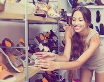 Vrouw die voor paar schoenen zorgen Royalty-vrije Stock Foto