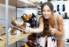 Vrouw die voor paar schoenen zorgen Stock Fotografie