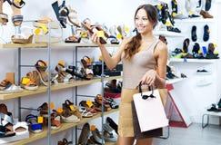 Vrouw die voor paar schoenen zorgen Royalty-vrije Stock Afbeelding