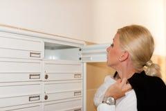 Vrouw die voor post in brievenbus zorgt Royalty-vrije Stock Foto
